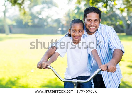 caring indian father helping his cute daughter ride a bike - stock photo