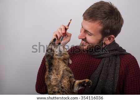 Caring man playing with cat - stock photo