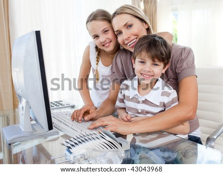 Caring mother and her children at a computer in the living-room
