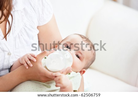 Caring mother feeding her adorable son in the kitchen at home - stock photo