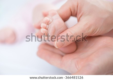 Caring mother holding foot of her infant