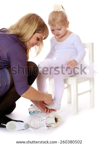 caring mother puts on skates his little beloved daughter - isolated on white. - stock photo