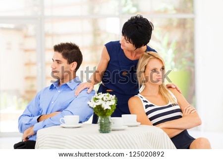caring mother reconciling fighting young couple - stock photo