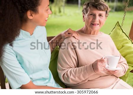 Caring nurse and elder woman in the garden - stock photo