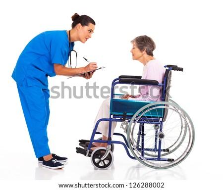 caring nurse helping senior patient filling medical form - stock photo