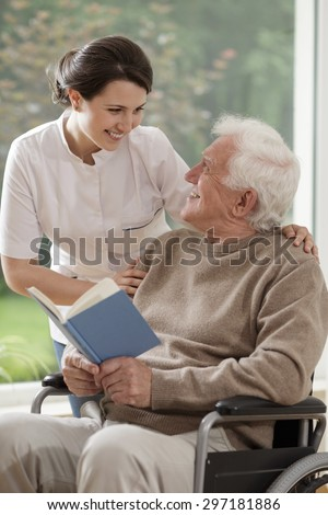 Caring nurse talking with senior disabled patient - stock photo