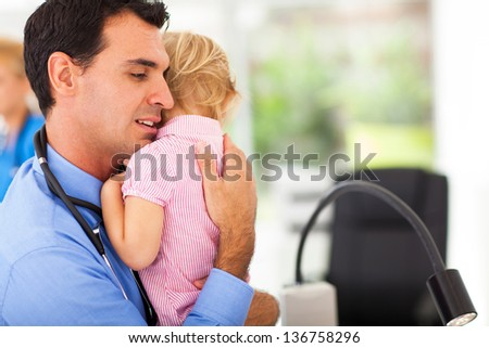 caring pediatrician hugging a sick baby girl - stock photo