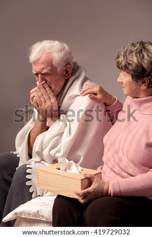 Caring senior wife and her ill husband sitting in a light interior - stock photo