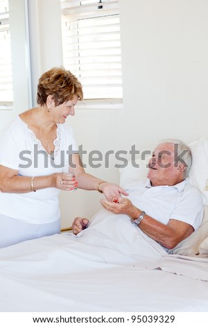 caring senior wife giving medicine to ill husband - stock photo