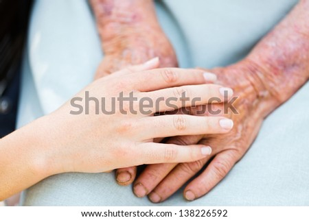 Caring woman hands over elderly hands being concept of trust and reliability. - stock photo