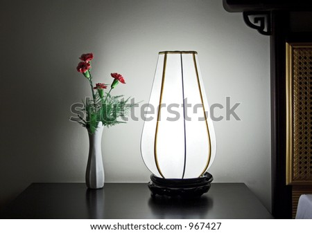 Carnation and lamp on night table - stock photo