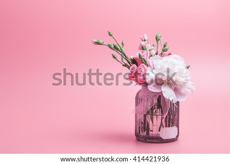 carnation with pink rose and pink peony on bottle with pink background - stock photo