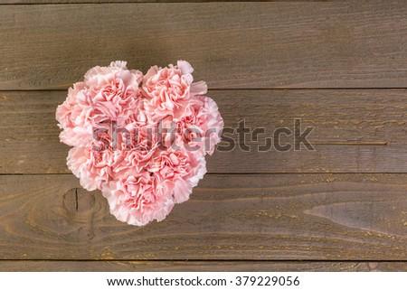 Carnations flowers in heart shape arrangment on wood board. - stock photo