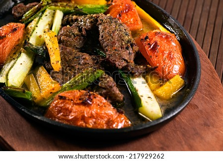 Carne Asada beef and vegetables (tomatoes, zucchini, yellow bell pepper, spring onions, garlic, seasonings & olive oil).  - stock photo