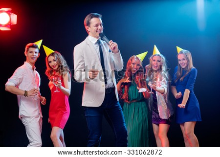 Carnival and party. Emcee with microphone. Group of cheerful friends dancing in nightclub. - stock photo