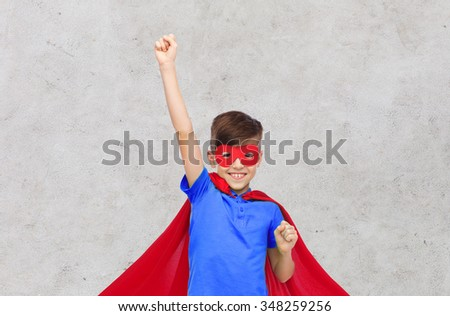 carnival, childhood, power, gesture and people concept - happy boy in red superhero cape and mask showing fists over gray concrete background - stock photo