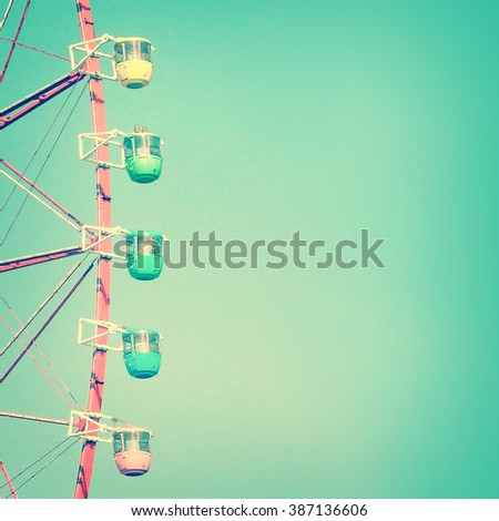Carnival ferris wheel and blue sky, vintage process - stock photo