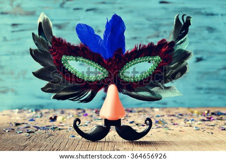 carnival mask ornamented with feathers of different colors and a fake nose and a a fake mustache, on a rustic wooden surface full of confetti - stock photo