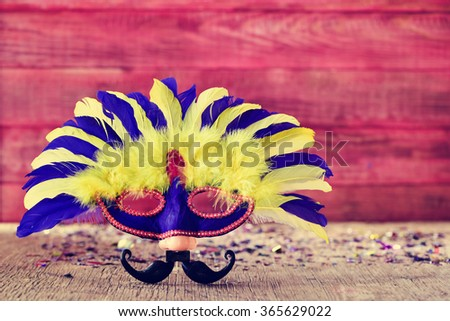 carnival mask ornamented with feathers of different colors and a fake nose and a fake mustache, on a rustic wooden surface full of confetti - stock photo