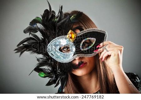 Carnival night life. Attractive woman face with hand holding mysterious mask on grey background in studio. - stock photo