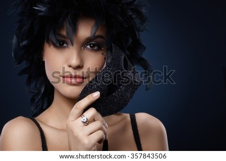 Carnival portrait of smiling beauty with elegant glittering mask and black feather boa. - stock photo