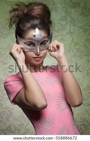 carnival shoot of sexy brunette girl masquerade with silver mask, posing with hair style and pink sexy dress  - stock photo