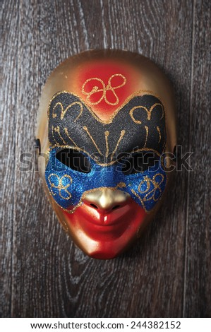 Carnival Venetian mask on a hardwood wall. Vertical photo - stock photo