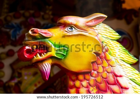 Carousel dragon; close-up portrait of traditional fairground carousel  galloping dragon  - stock photo