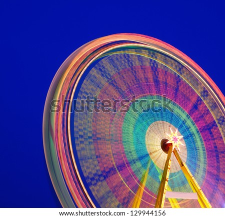 Carousel. Ferris Wheel on a blue background. Long time exposure. - stock photo