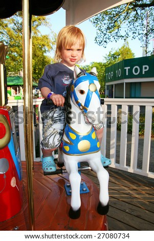 carousel merry-go-round in theme park. Child on horse roundabout - stock photo