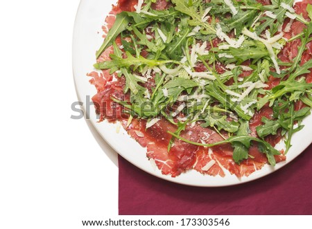 carpaccio of beef with rucola and Parmesan on red napkin - stock photo