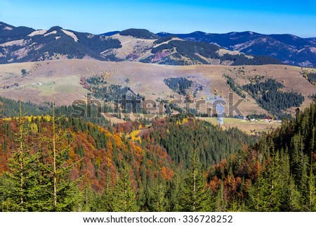 Carpathian Mountains Autumnal Panorama Fir Pine Forest with some Aspen and Birches Bright Autumnal Colors Local Village Making Column of Smoke - stock photo