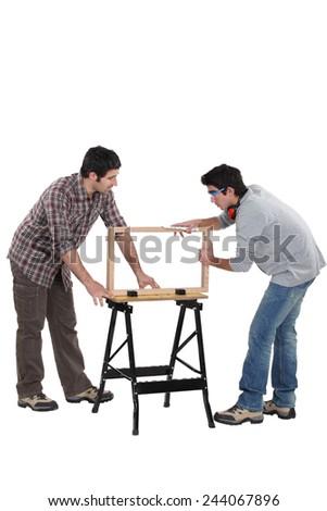 Carpenter and teenage helper - stock photo