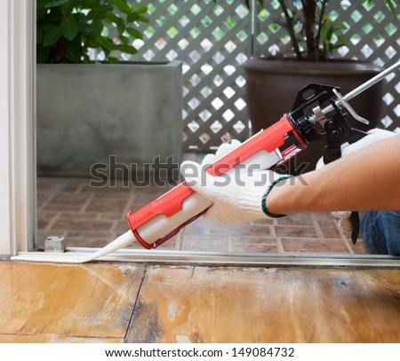 Carpenter applies silicone caulk on the wooden floor for sealant waterproof - stock photo