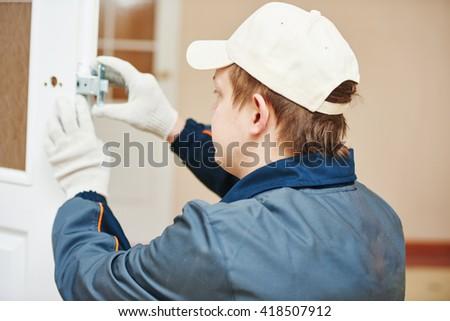 carpenter at door lock installation - stock photo