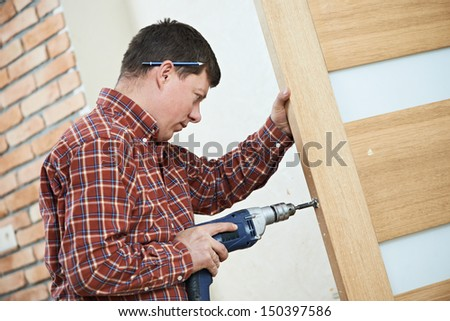 carpenter at lock installation with electric drill into interior wood door - stock photo