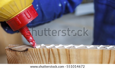 Carpenter at work using glue in his workshop.