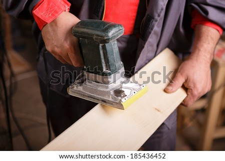 Carpenter at work with the sander on a wooden board - stock photo