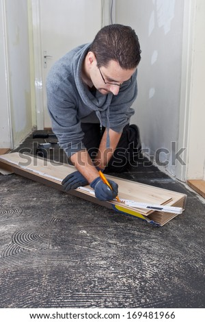 Carpenter bending down in a passage measuring new wooden floor boards during renovations and construction - stock photo