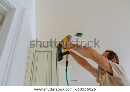Nail gun stock images royalty free images vectors shutterstock carpenter brad using nail gun to crown moulding on kitchen cabinets framing trim with the prinsesfo Image collections