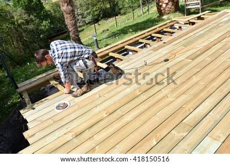 Carpenter building wooden deck  - stock photo