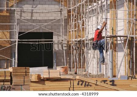 Carpenter climbing down scaffolding at a construction scene. - stock photo