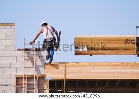 Carpenter climbing up ladder at a construction scene. - stock photo