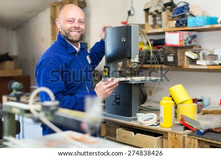 Carpenter cutting a wooden workpiece on an electical jigsaw