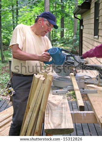 Carpenter cutting balusters for a deck railing with a chop saw - stock photo