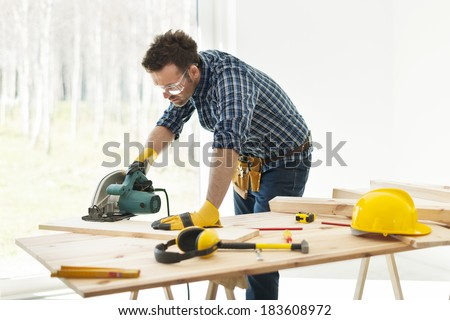 Carpenter cutting plank by circular saw  - stock photo