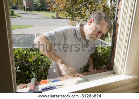Carpenter cutting wood needed to replace rotten wood on exterior of home - stock photo