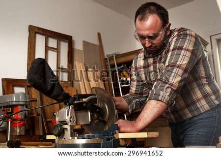 Carpenter cutting wooden plank with circular saw in his workshop. - stock photo