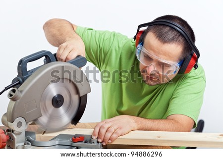 Carpenter cutting wooden plank with circular saw wearing safety equipment