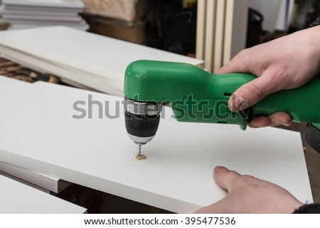 Carpenter drills a hole in the component parts of a white kitchen cabinet for fastening pins wall cabinets. Small wholesale furniture factory, part of the technological assembly line. - stock photo